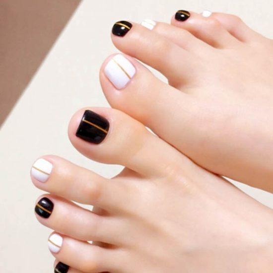 สีเล็บเท้าแฟชั่นสีดำสลับสีขาวคาดกลางเล็บสีทองแบบแปลกตา
