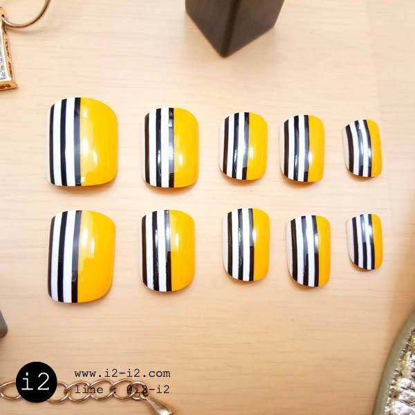 เล็บปลอมแฟชั่นสีเหลืออมส้มเพ้นท์ลายขอบเล็บลายทางสีขาวตัดดำสวยทันสมัย